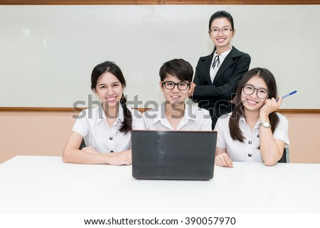 Asian teacher assisting student using laptop at desk in classroom - stock photo
