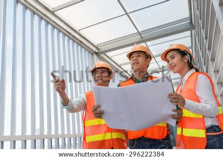 Asian team of engineers discussing construction project - stock photo