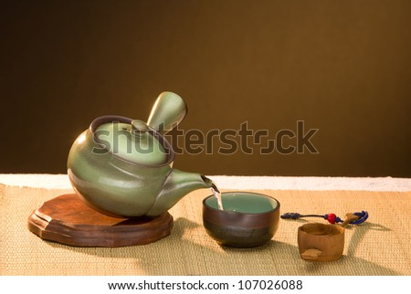 Asian teapot pouring tea to cup