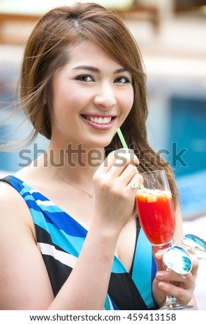 Asian teen laughing while drinking fruit punch cocktail