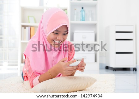 Asian teen texting a message with her cell phone. Southeast Asian teenager at home. Muslim teenage girl living lifestyle. - stock photo