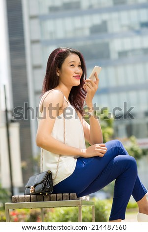 Asian teenage girl sitting on the bench and talking on the phone - stock photo