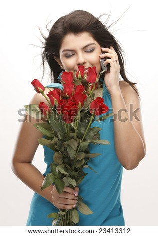 Asian teenage girl smelling the red roses - stock photo