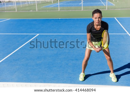 Asian tennis player woman ready to play on blue hard court outdoor in summer in position holding racket wearing outfit with skirt and shoes. Female athlete determination and concentration concept. - stock photo