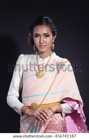Asian Thai Woman in Traditional Costume of Thailand in ancient house at Ayutthaya, Tan Skin, Studio lighting, dark background