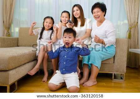 Asian three generations family watching television and shouting on their home side in a sporting competition - stock photo