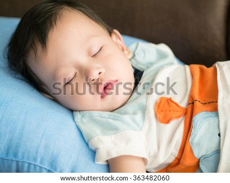 Asian toddler fell into a slumber on bed. - stock photo