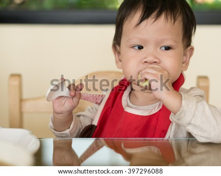 Asian toddler learn to eat meal herself. - stock photo