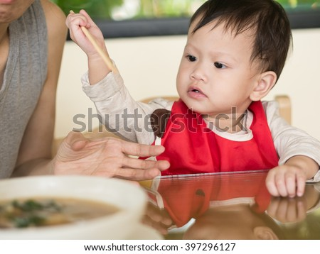 Asian toddler learn to eat meal herself holding chopsticks.