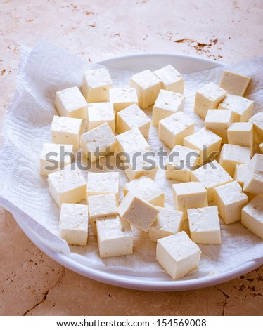 Asian tofu cubes or soybean curd drying on a paper towel before cooking. - stock photo