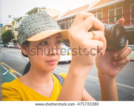 Asian tourist woman is taking a photo of a place.