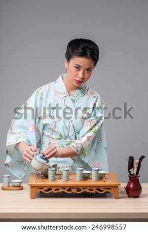 Asian traditions and culture. Young beautiful Japanese woman in traditional kimono getting ready to perform tea ceremony with tea tools on the table against grey background