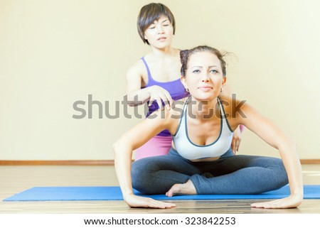 Asian trainer conducts classes of group yoga indoor, at yoga class. Concept of a healthy lifestyle and the right attitude to life