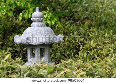 Asian-type stone lantern on shrub - stock photo