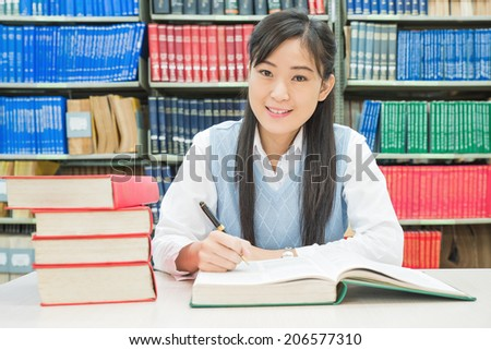 Asian university student reading book in library at university - stock photo