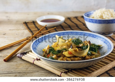 Asian  vegetable dish with chopsticks, rice and soy sauce on a bamboo mat and a rustic wooden table, vegetarian and healthy, selected focus, narrow depth of field - stock photo