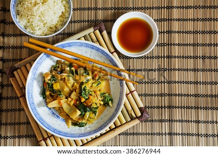 Asian vegetable dish with chopsticks, rice and soy sauce on a bamboo mat with copy space, view from above,  selected focus - stock photo