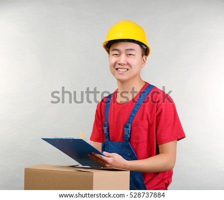 Asian warehouse worker with clipboard and carton box, on light background