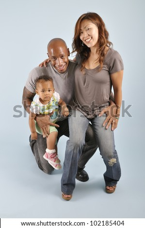 Asian wife, African American husband posing with their mixed race infant girl. - stock photo