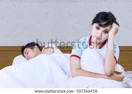 Asian wife is having insomnia while husband asleep in house bedroom