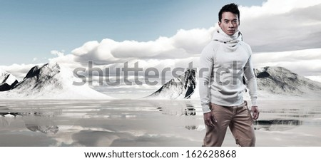 Asian winter fashion man in snow mountain landscape. Wearing white sweater and scarf and brown trousers. - stock photo