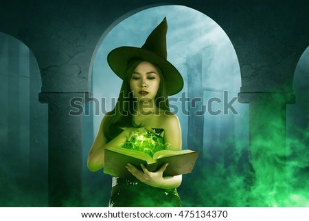 Asian witch woman holding the book in empty room, horror situation with fog background