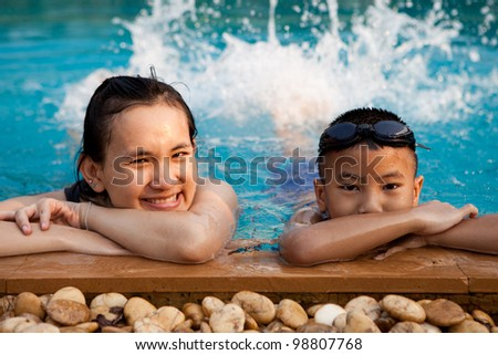 Asian woman and boy in swimming pool - stock photo