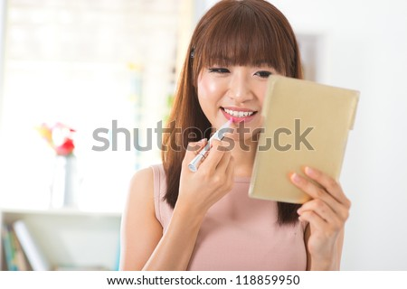 Asian woman applying cosmetic with applicator. Make-up treatment in her bedroom. - stock photo
