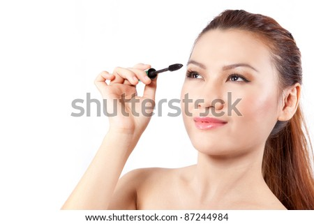 asian woman applying mascara, isolated on white