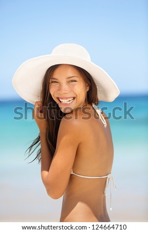 Asian woman beach portrait. Happy lifestyle photo of mixed race Asian Chinese / Caucasian young lady in bikini smiling pretty wearing beach hat on summer holiday vacation. - stock photo