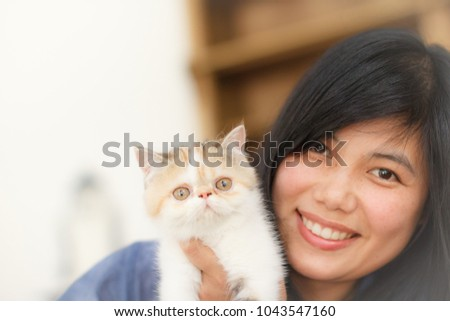 Asian Woman Beautiful Face is Holding a Kitten in Living Room. Idea Concept for Love a Pet. Copy Space for Text.