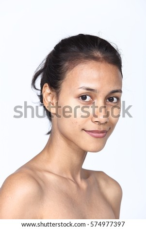 Asian Woman before make up. no retouch, fresh face with acne in studio lighting gray background