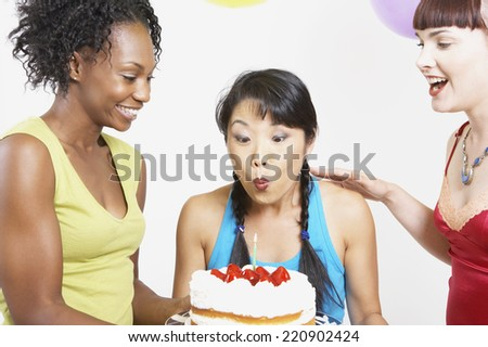 Asian woman blowing out candle on cake - stock photo