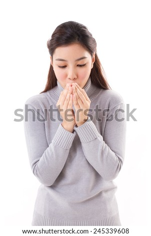 asian woman blowing warm air from her mouth to her hand, enjoy winter - stock photo