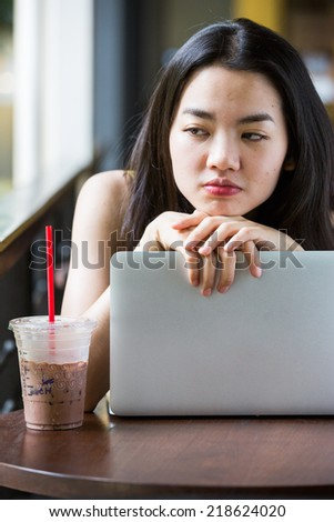 Asian woman boredly using a notebook - stock photo