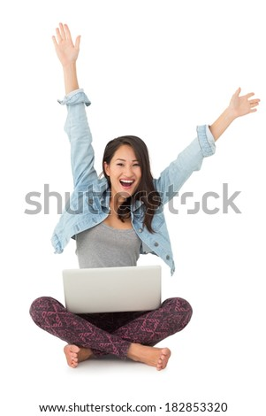 Asian woman cheering at camera with laptop sitting on floor on white background