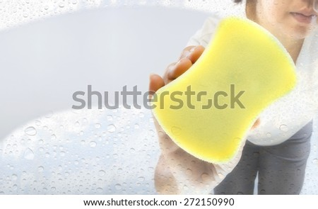 Asian woman cleaning window glass - stock photo
