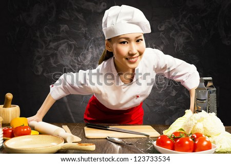 Asian woman cook leaned over the table and looking into the camera - stock photo