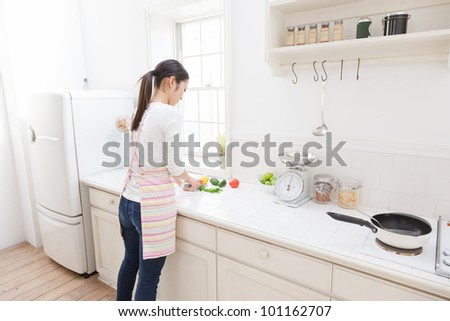 Asian woman cutting vegetables in the kitchen