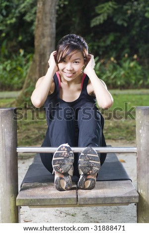 asian woman doing sit ups at a fitness corner with a smile