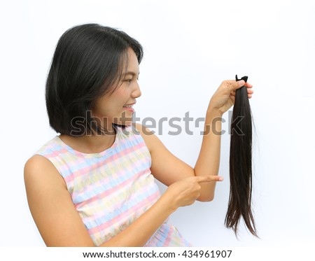 Asian woman donating her hair to cancer patients - holding her former hair after a haircut, generously donating her long hair for making wigs for cancer patients who lost their hair