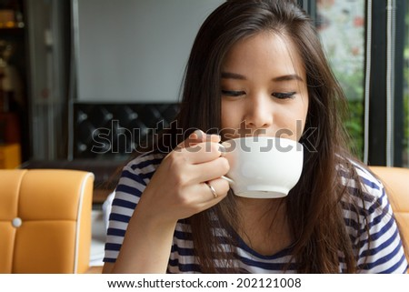 Asian woman drinking coffee in a cafe - stock photo