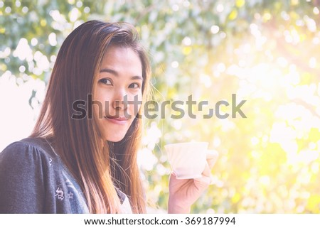 Asian woman drinking coffee in sunshine light enjoying her morning coffee. - stock photo