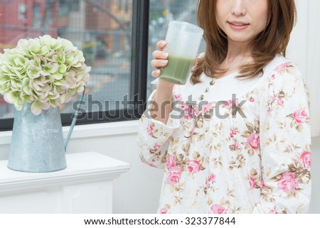 asian woman drinks green juice