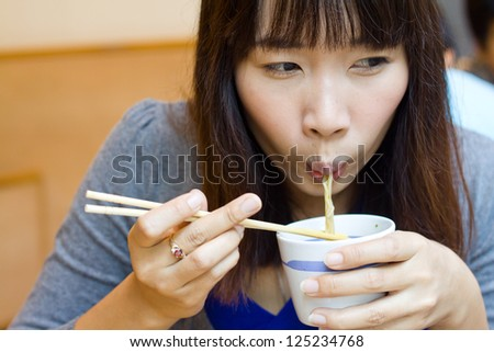 Asian woman  eating japanese noodle in  restaurant - stock photo