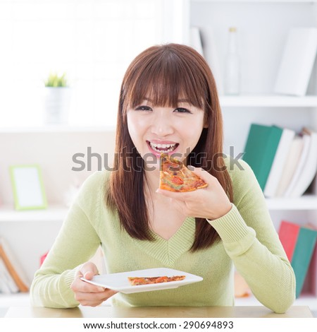Asian woman eating pizza at home. Female living lifestyle indoors.