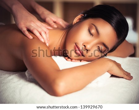 Asian woman enjoying a back massage at a spa centre. - stock photo