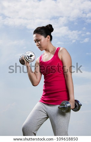 Asian woman exercising with dumb bell weights outside.