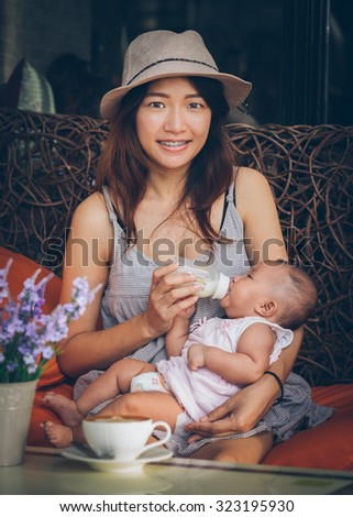 Asian woman feeding her daughter with a bottle milk, see a coffee cup on a desk in front of her. Vintage retro style photo with color filters, vignette effect, and some fine film noise added. - stock photo
