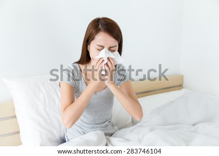 Asian woman feeling unwell and sneeze on bed - stock photo